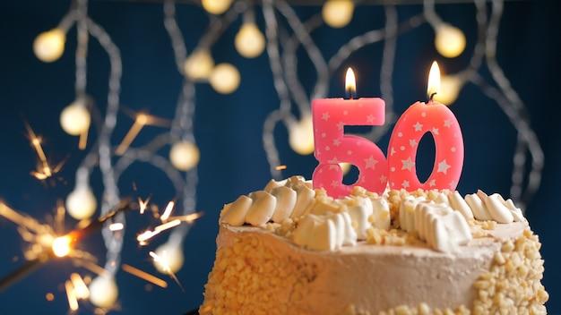 Gâteau d'anniversaire avec 50 bougies roses numérotées et cierge magique brûlant sur fond bleu. fermer