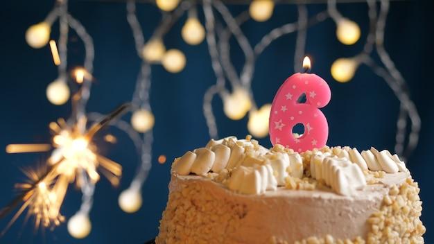 Gâteau d'anniversaire avec 6 bougies roses et cierge magique brûlant sur fond bleu. fermer
