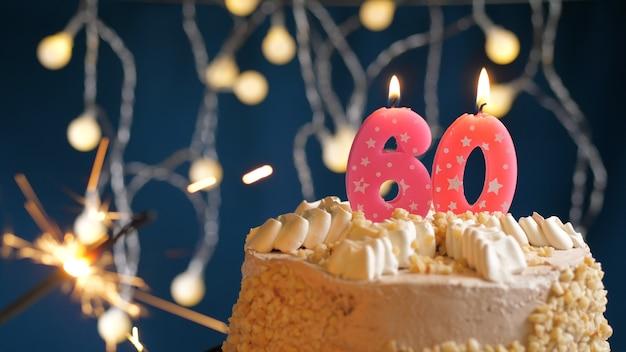 Gâteau d'anniversaire avec 60 bougies roses et cierge magique brûlant sur fond bleu. fermer