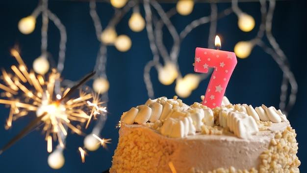 Gâteau d'anniversaire avec 7 bougies roses et cierge magique brûlant sur fond bleu. fermer