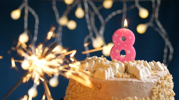 Gâteau d'anniversaire avec 8 bougies roses et cierge magique brûlant sur fond bleu. fermer