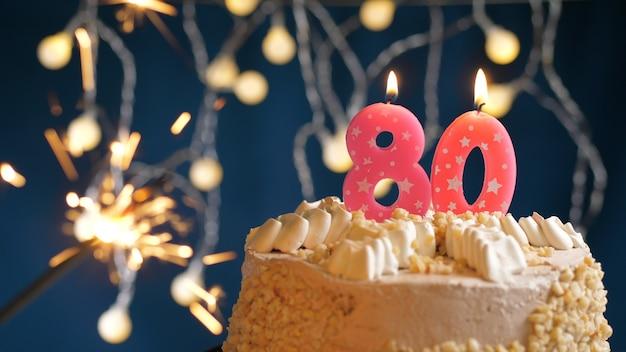 Gâteau d'anniversaire avec 80 bougies roses et cierge magique brûlant sur fond bleu. fermer
