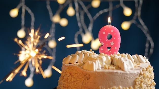 Gâteau d'anniversaire avec 9 bougies roses et cierge magique brûlant sur fond bleu. fermer