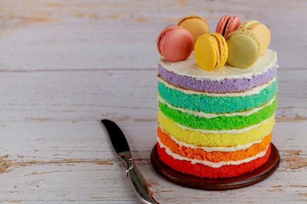 Gâteau d'anniversaire arc-en-ciel décoré de macarons de couleur.