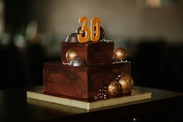 Gâteau d'anniversaire au chocolat avec un numéro trente. décoré de boules de chocolat doré. bon anniversaire