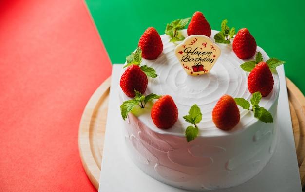 Gâteau d'anniversaire blanc avec décoration aux fraises sur le gâteau, fond de concept alimentaire.