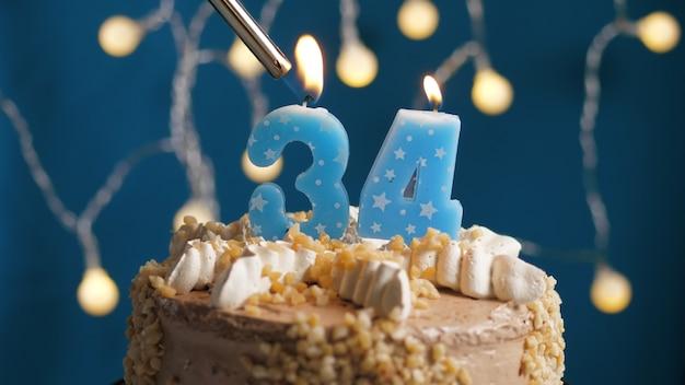 Gâteau d'anniversaire avec bougie à 34 chiffres sur fond bleu incendié par un briquet. fermer