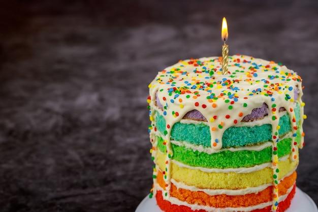 Gâteau d'anniversaire avec bougie allumée et pépites de sucre.