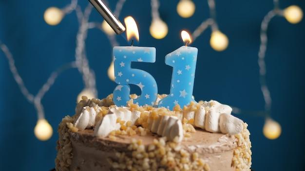 Gâteau d'anniversaire avec bougie numéro 51 sur fond bleu incendié par un briquet. fermer
