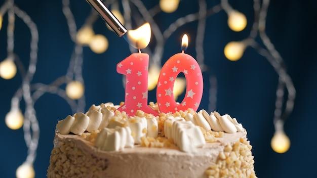 Gâteau d'anniversaire avec bougie rose à 10 chiffres sur fond bleu incendié par un briquet. vue rapprochée