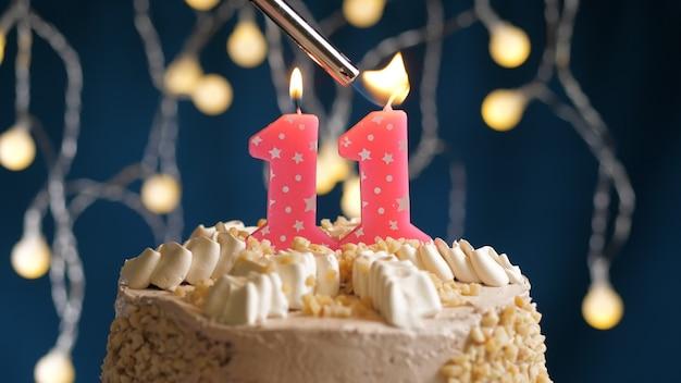Gâteau d'anniversaire avec une bougie rose à 11 chiffres sur fond bleu incendié par un briquet. vue rapprochée
