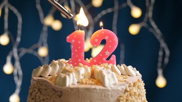 Gâteau d'anniversaire avec bougie rose à 12 chiffres sur fond bleu incendié par un briquet. vue rapprochée