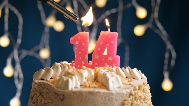 Gâteau d'anniversaire avec une bougie rose à 14 chiffres sur fond bleu incendié par un briquet. vue rapprochée