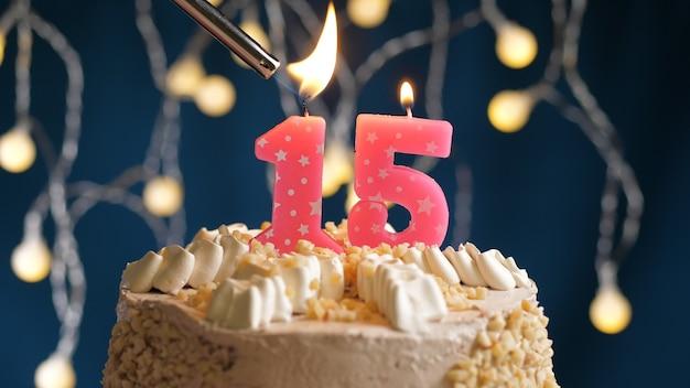 Gâteau d'anniversaire avec une bougie rose à 15 chiffres sur fond bleu incendié par un briquet. vue rapprochée