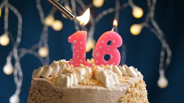 Gâteau d'anniversaire avec bougie rose à 16 chiffres sur fond bleu incendié par un briquet. vue rapprochée