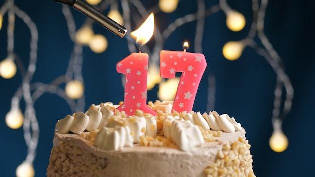 Gâteau d'anniversaire avec bougie rose à 17 chiffres sur fond bleu incendié par un briquet. vue rapprochée