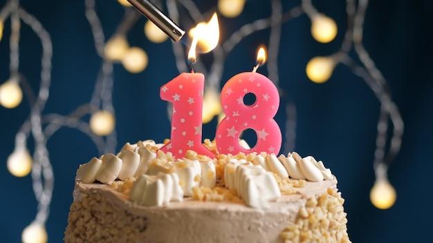 Gâteau d'anniversaire avec bougie rose à 18 chiffres sur fond bleu incendié par un briquet. vue rapprochée