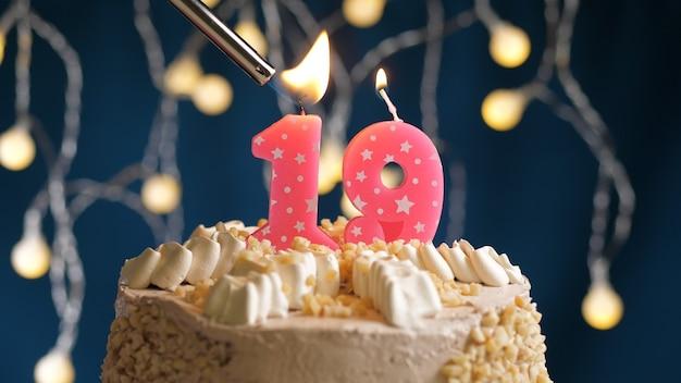 Gâteau d'anniversaire avec bougie rose à 19 chiffres sur fond bleu incendié par un briquet. vue rapprochée