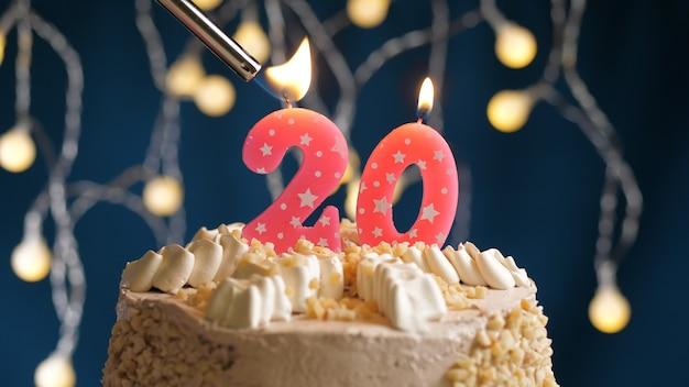 Gâteau d'anniversaire avec bougie rose à 20 chiffres sur fond bleu incendié par un briquet. vue rapprochée