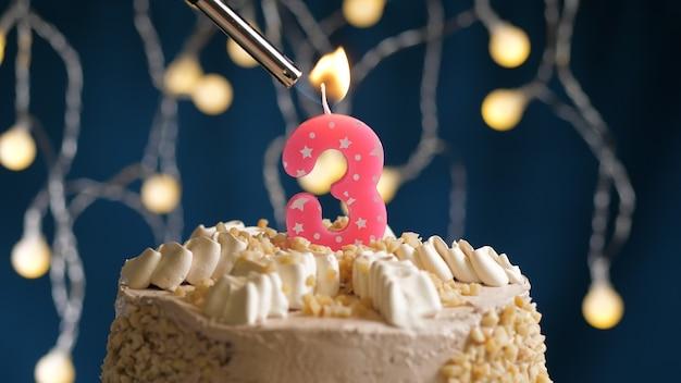 Gâteau d'anniversaire avec bougie rose à 3 chiffres sur fond bleu incendié par un briquet. vue rapprochée