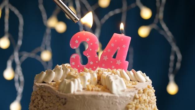 Gâteau d'anniversaire avec bougie rose à 34 chiffres sur fond bleu incendié par un briquet. vue rapprochée