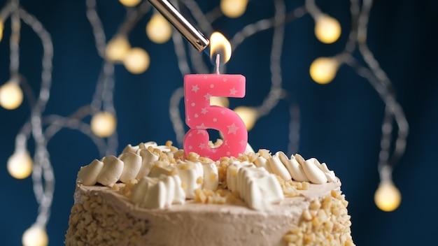Gâteau d'anniversaire avec bougie rose à 5 chiffres sur fond bleu incendié par un briquet. vue rapprochée