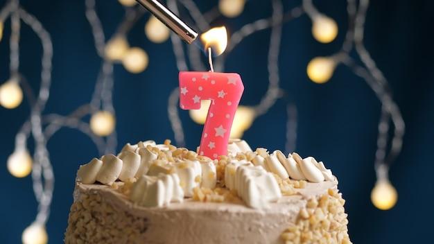 Gâteau d'anniversaire avec bougie rose à 7 chiffres sur fond bleu incendié par un briquet. vue rapprochée