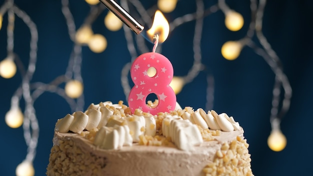 Gâteau d'anniversaire avec bougie rose à 8 chiffres sur fond bleu incendié par un briquet. vue rapprochée