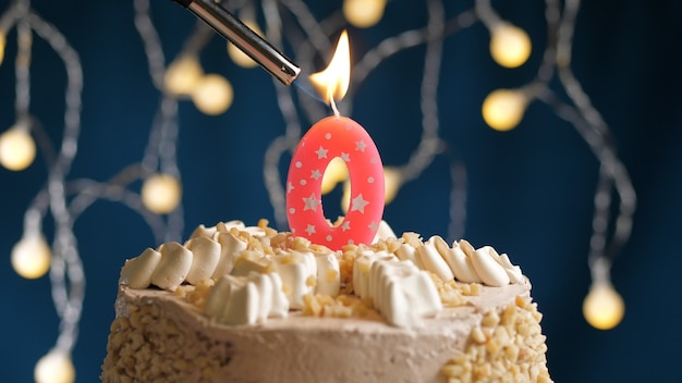 Gâteau d'anniversaire avec bougie rose numéro 0 sur fond bleu incendié par un briquet. vue rapprochée