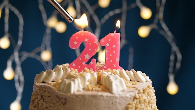 Gâteau d'anniversaire avec bougie rose numéro 21 sur fond bleu incendié par un briquet. vue rapprochée