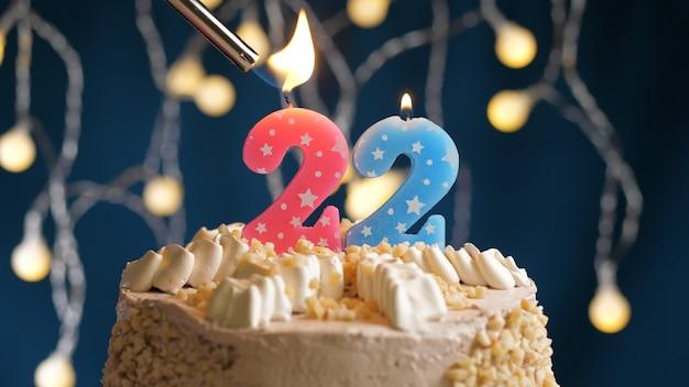 Gâteau d'anniversaire avec bougie rose numéro 22 sur fond bleu incendié par un briquet. vue rapprochée