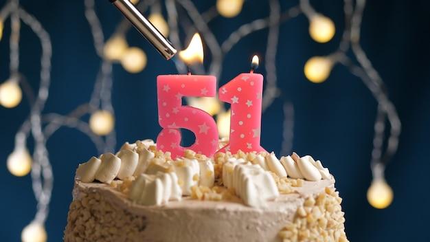 Gâteau d'anniversaire avec bougie rose numéro 51 sur fond bleu incendié par un briquet. vue rapprochée
