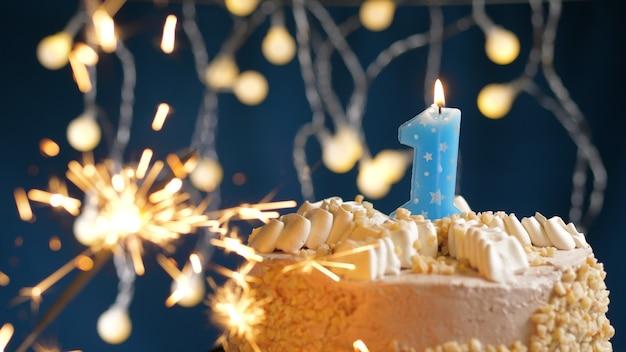 Gâteau d'anniversaire avec bougies à 1 numéro et cierge magique brûlant sur fond bleu. fermer