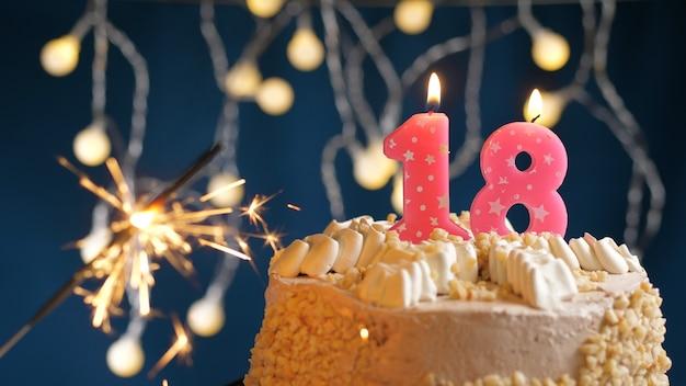 Gâteau d'anniversaire avec bougies roses à 18 chiffres et cierge magique brûlant sur fond bleu. fermer