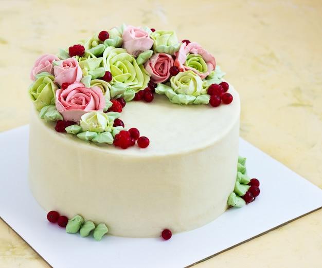 Gâteau d'anniversaire avec des fleurs rose sur la lumière