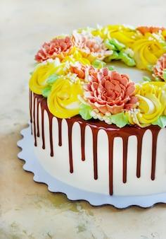 Gâteau d'anniversaire avec des fleurs rose sur une surface blanche