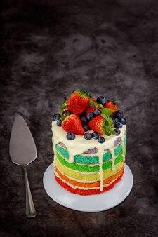 Gâteau d'anniversaire multicolore décoré de baies fraîches.