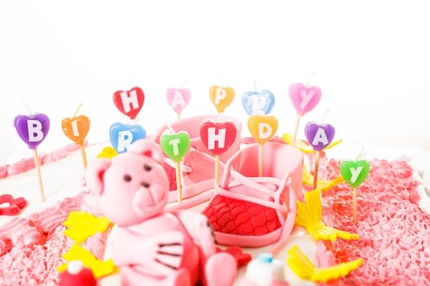 Un gâteau d'anniversaire rose pour enfants avec des bougies de joyeux anniversaire