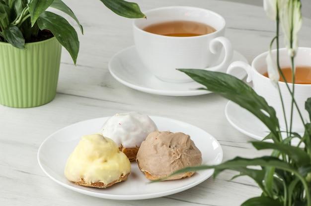 Gâteau sur une assiette et deux tasses de thé sur la table avec des fleurs