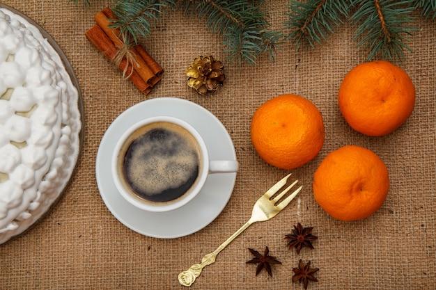 Gâteau au biscuit décoré de crème fouettée, tasse de café, fourchette, oranges, anis étoilé et cannelle avec branche d'épinette sur un sac. vue de dessus.