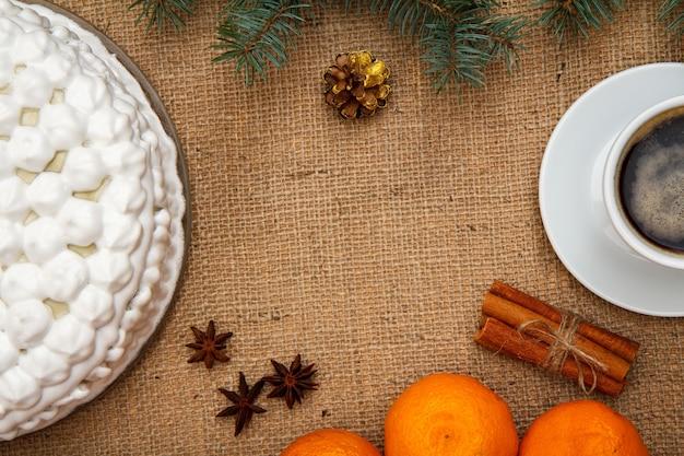 Gâteau au biscuit décoré de crème fouettée, tasse de café, oranges, anis étoilé et cannelle avec branche d'épinette sur un sac. vue de dessus.