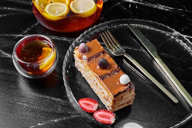 Gâteau au caramel avec du jus sur fond noir.