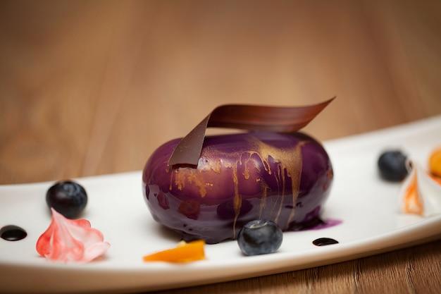 Gâteau au chocolat arrosé de glaçage or violet sur un fond en bois