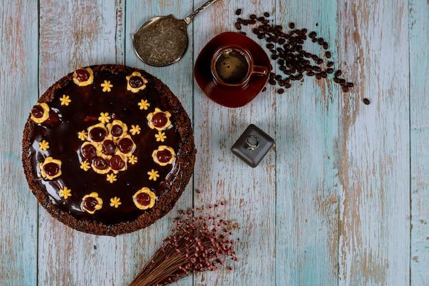 Gâteau au chocolat au rhum avec café et anneau sur table en bois