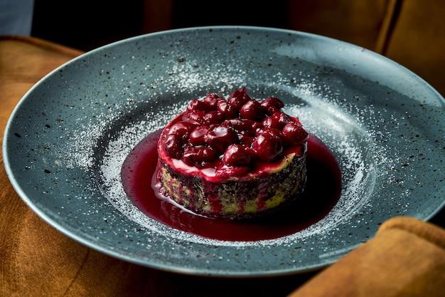 Gâteau au chocolat aux cerises et confiture, crème anglaise, servi dans une assiette bleue. restaurant servant des desserts