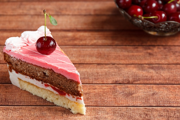 Gâteau au chocolat aux cerises sur fond en bois.