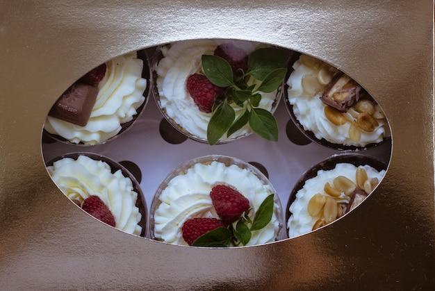 Gâteau au chocolat aux framboises avec de la crème fouettée dans une boîte cadeau
