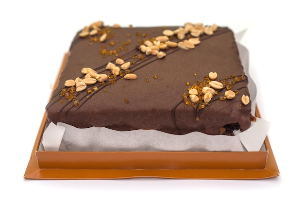 Gâteau au chocolat aux noix et caramel dans une boîte en carton isolé sur un blanc.