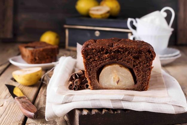 Gâteau au chocolat aux poires et à la cannelle sur fond de bois ancien