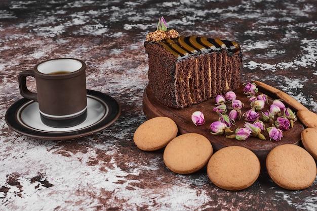 Gâteau au chocolat et biscuits sur une planche de bois.